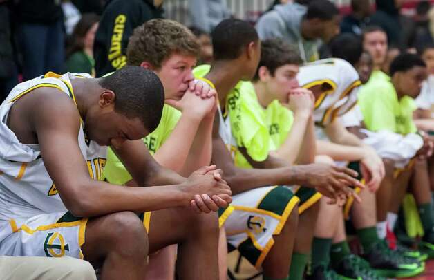 A dejected Trinity Catholic high school team sits on the bench as the Bridgeport Central high school team celebrates winning the FCIAC boy's basketball championship game held at Fairfield Warde high school, Fairfield, CT on Thursday February 28th, 2013. Photo: Mark Conrad / Connecticut Post Freelance