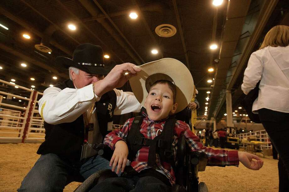 Zach Christian has his hat put on by his rodeo buddy Lee Ewing during the 2013 Lil' Rustlers Rodeo, an event for children with special needs at Reliant Center Thursday, Feb. 28, 2013, in Houston. 