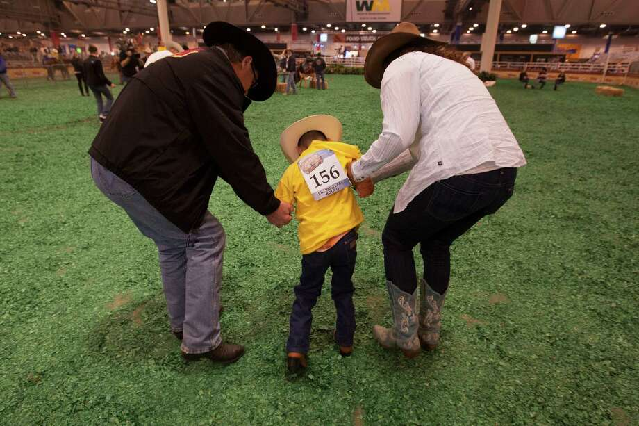 Jeremy Martinez, 7, gets a hand from his rodeo buddies Tim Broussard, left, and Darcy Williams. Photo: Johnny Hanson, Houston Chronicle / © 2013  Houston Chronicle