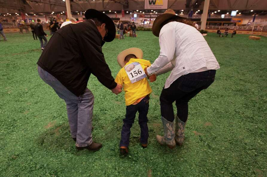 Jeremy Martinez, 7, gets a hand from his rodeo buddies Tim Broussard, left, and Darcy Williams.