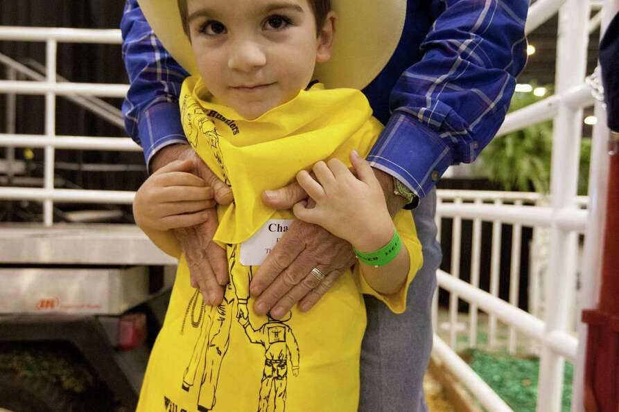 Chance Biehn his held by his rodeo buddy Kim Raymond.