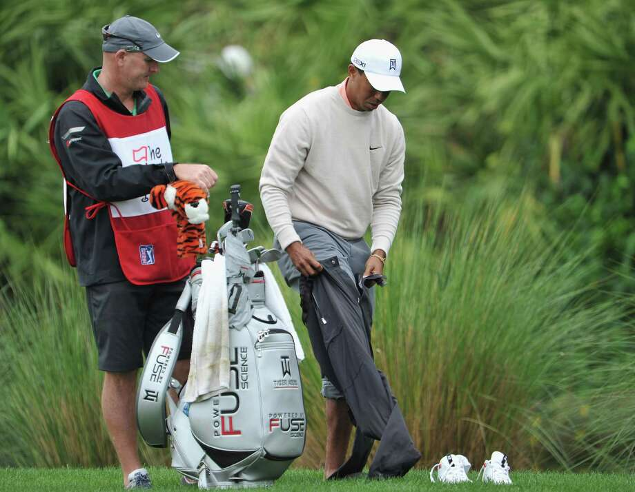 Tiger Woods, right, dons his rain pants after taking off his shoes and socks to play his half-submerged ball during Thursday's round at the Honda Classic. Photo: Stuart Franklin, Staff / 2013 Getty Images