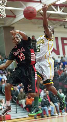 Bridgeport Central high school's ShaQuan Bretoux blocks a shot by Trinity Catholic high school's Brandon Wheeler in the FCIAC boy's basketball championship game held at Fairfield Warde high school, Fairfield, CT on Thursday February 28th, 2013. Photo: Mark Conrad / Connecticut Post Freelance