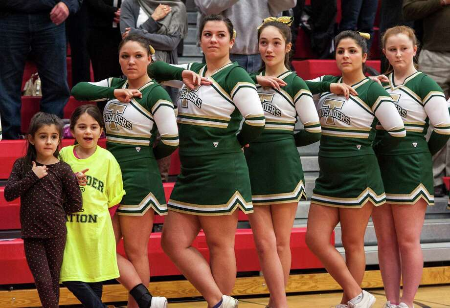 Mia Carrizzo and Lily Hajjar join the Trinity Catholic high school cheerleaders during the National Anthem at the start of the FCIAC boy's basketball championship game held at Fairfield Warde high school, Fairfield, CT on Thursday February 28th, 2013. Photo: Mark Conrad / Connecticut Post Freelance