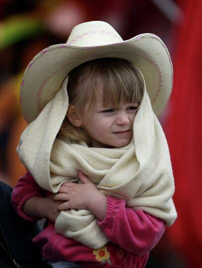 Madeline Yeager, 3, of Conroe huddles in her scarf under her cowboy hat as she and her family brave