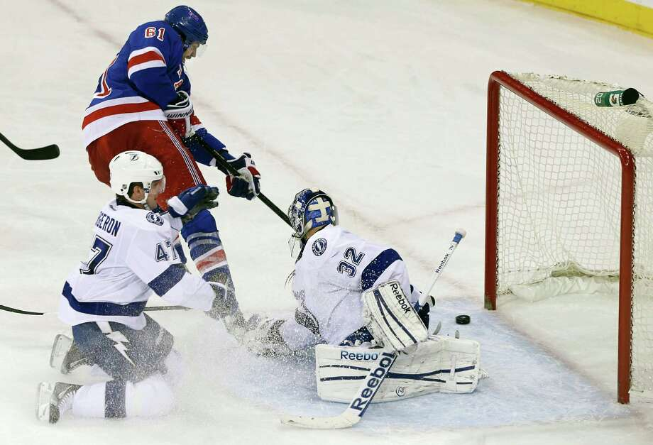 New York Rangers' Rick Nash (61) shoots the puck past Tampa Bay Lightning goalie Mathieu Garon (32) and Marc-Andre Bergeron (47) to score during the third period of an NHL hockey game on Thursday, Feb. 28, 2013, in New York. The Rangers won the game 4-1. (AP Photo/Frank Franklin II) Photo: Frank Franklin II