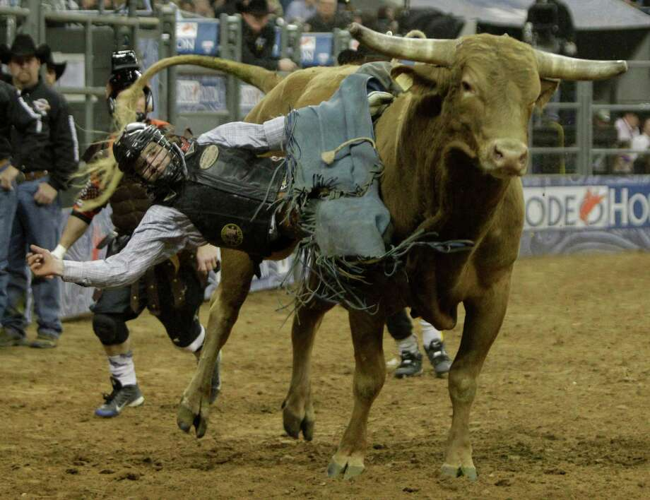 Clayton Savage of Casper, WY gets sideways on a bull named Big Country but stays on to score 72.5 for second place during round 1 of the Super Series II  of RodeoHouston at at the Houston Livestock Show and Rodeo at Reliant Stadium Thursday, Feb. 28, 2013, in Houston. Photo: Melissa Phillip, Houston Chronicle / © 2013  Houston Chronicle