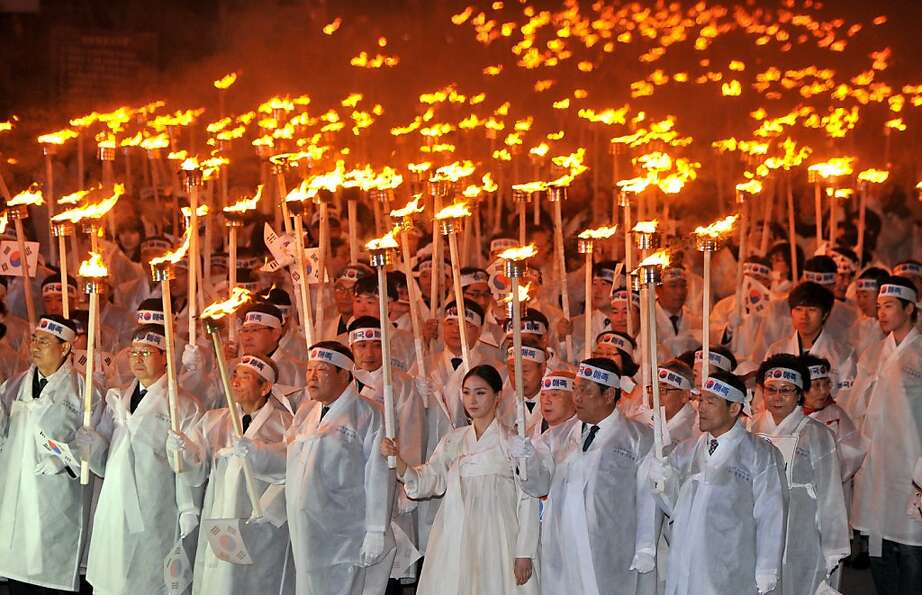 South Koreans wearing traditional costumes carry torches in their hands to celebrate the March 1 Ind