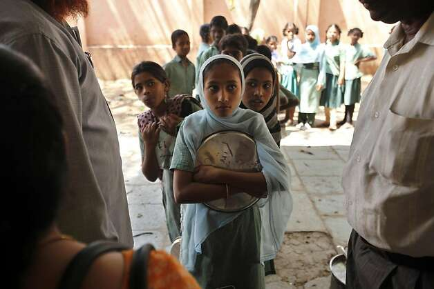 Indian children stand to receive a free midday meal at a government school in Hyderabad, India, Thursday, Feb. 28, 2013. Finance Minister Palaniappan Chidambaram has unveiled the national budget with a promise to set Asia's third largest economy back on a path of high growth and to check runaway inflation and the fiscal deficit. With the country headed for general elections in 2014, government spending on costly social programs was projected to go up substantially. The budget has assigned 100 billion rupees for an ambitious food security program, which will provide subsidized food to the poor. Photo: Mahesh Kumar A, Associated Press