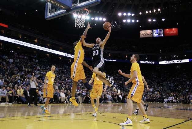 Manu Ginobili #20 of the San Antonio Spurs goes up for a shot Golden State Warriors at Oracle Arena on February 22, 2013 in Oakland, California. The Warriors are wearing new short-sleeved uniforms for the first time. The Warriors won the game in overtime. Photo: Ezra Shaw, Getty Images / 2013 Getty Images