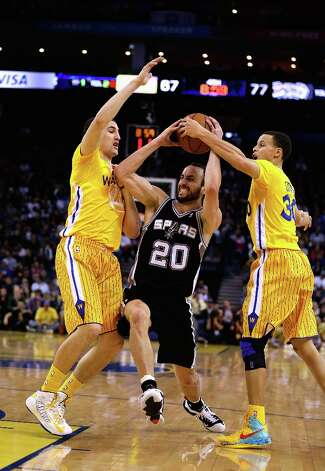 Manu Ginobili #20 of the San Antonio Spurs drives between Klay Thompson #11 and Stephen Curry #30 of the Golden State Warriors at Oracle Arena on February 22, 2013 in Oakland, California. The Warriors are wearing new short-sleeved uniforms for the first time. The Warriors won the game in overtime. Photo: Ezra Shaw, Getty Images / 2013 Getty Images