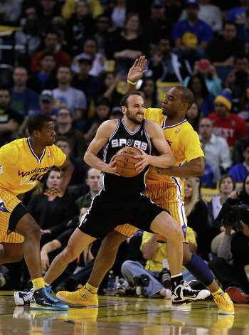 Manu Ginobili #20 of the San Antonio Spurs drives between Harrison Barnes #40 and Carl Landry #7 of the Golden State Warriors at Oracle Arena on February 22, 2013 in Oakland, California. The Warriors are wearing new short-sleeved uniforms for the first time. The Warriors won the game in overtime. Photo: Ezra Shaw, Getty Images / 2013 Getty Images
