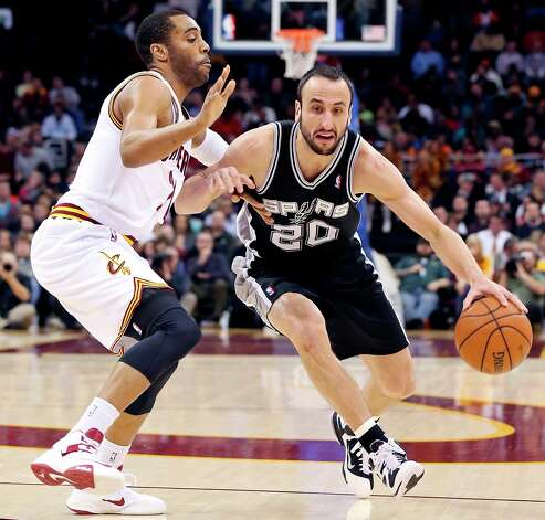 The Spurs' Manu Ginobili looks for room around Cleveland Cavaliers' Wayne Ellington during first half action Wednesday Feb. 13, 2013 at the Quicken Loans Arena in Cleveland, Ohio. Photo: Edward A. Ornelas, San Antonio Express-News / © 2013 San Antonio Express-News