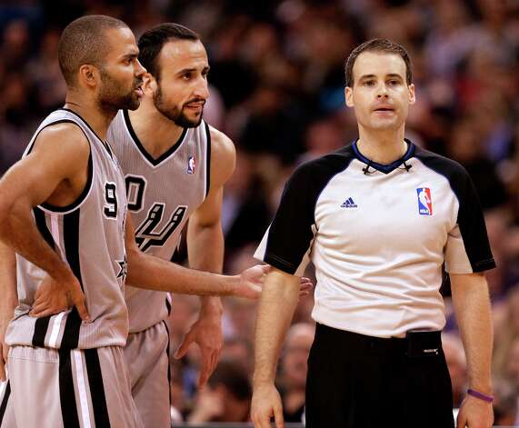 The Spurs' Tony Parker, left, and Manu Ginobili, center, question Official Mark Lindsay about a call during the fourth   quarter in Sacramento, Calif., Tuesday, Feb. 19, 2013.  The Spurs won 108-102. Photo: Rich Pedroncelli, Associated Press / AP