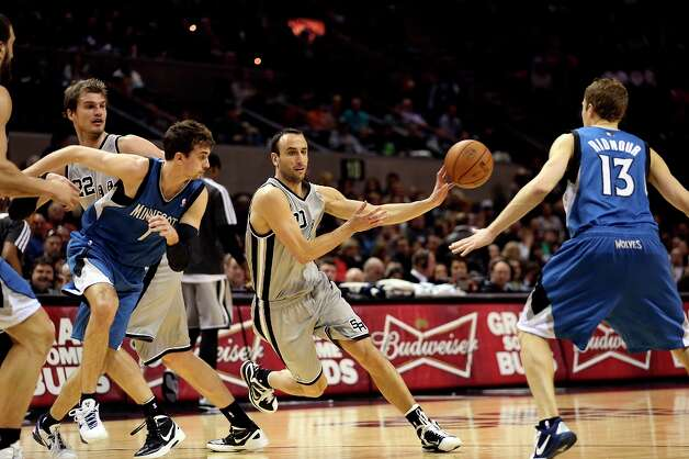 The Spurs' Manu Ginobili pass the ball as Minnesota Timberwolves' Alexey Shved, left, and Luke Ridnour defend in the first half at the AT&T Center, Sunday, Jan. 13, 2013. Ginobili left in the second quarter with a strained leg muscle. Photo: Jerry Lara, San Antonio Express-News / © 2013 San Antonio Express-News