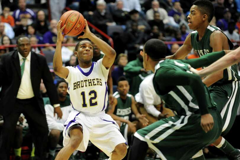 CBA's Tyrell Ramsey (12), left, looks to pass as Green Tech's Jizziah Carr (11), center, and David C