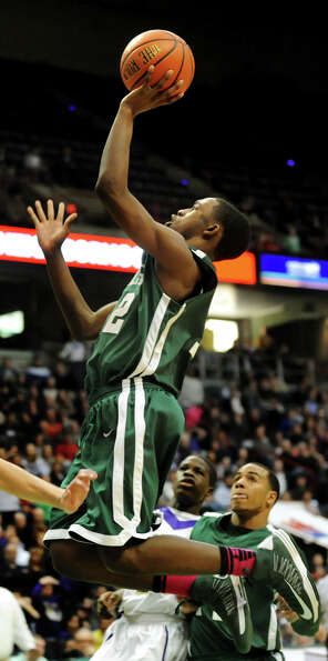 Green Tech's Jamil Hood Jr. (12) jumps and makes the shot to make the score 64-60 during their Class