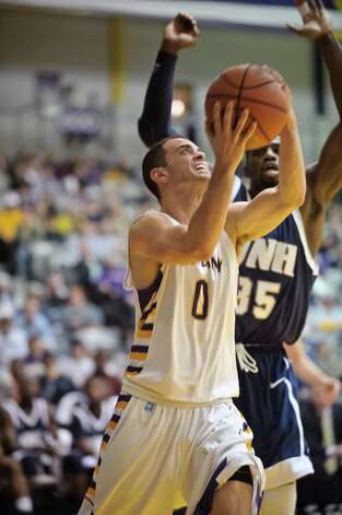 University at Albany's Jacob Iati shoots for a basket past UNH's Jeron Trotman,  Thursday Feb. 28, 2013, at SEFCU arena in Albany, N.Y.  (Eric Jenks/Special to the Times Union) Photo: Eric Jenks / All rights reserved Eric Jenks 2013 AWASOS.COM