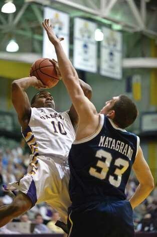 University at Albany's Mike Black leans back during a successful shot on the basket past UNH's Chris Matagrano,  Thursday Feb. 28, 2013, at SEFCU arena in Albany, N.Y.  (Eric Jenks/Special to the Times Union) Photo: Eric Jenks / All rights reserved Eric Jenks 2013 AWASOS.COM