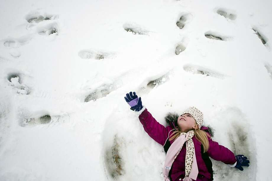 Kindergartner Paige Chisholm, 6,  reaches as far as she can as her cap falls over her face while making a snow angel on Thursday, Feb. 28, 2013 during recess at Cook Elementary School in Grand Blanc, Mich. Photo: Jake May, Associated Press