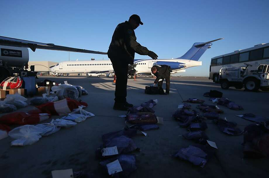 A security contractor hired by U.S. Immigration and Customs Enforcement (ICE), counts bags of personal possessions of Honduran immigration detainees before their deportation flight bound for San Pedro Sula, Honduras on February 28, 2013 in Mesa, Arizona. ICE operates 4-5 flights per week from Mesa to Central America, deporting hundreds of undocumented immigrants detained in western states of the U.S. With the possibility of federal budget sequestration, ICE released 303 immigration detainees in the last week from detention centers throughout Arizona. More than 2,000 immigration detainees remain in ICE custody in the state. Most detainees typically remain in custody for several weeks before they are deported to their home country, while others remain for longer periods while their immigration cases work through the courts. (Photo by John Moore/Getty Images) Photo: John Moore, Getty Images