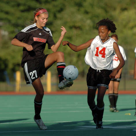 Fairfield Warde's #27 Elise Finzi, left, controls the ball as Central's #14 Amanda McKenzie comes in to intercept, during soccer action at Central High School in Bridgeport, Conn. on Tuesday September 21, 2010. Photo: Christian Abraham, ST / Connecticut Post