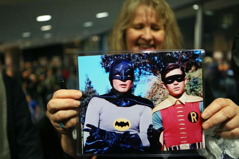 Laurie Staples holds a photo of Adam West, who played Batman, and Burt Ward, who played Robin during Emerald CIty Comicon's A Gotham Night in the Emerald City at Seattle's Cinerama. The actors attended a viewing of the 1966 theatrical Batman film on Friday, February 28, 2013 to help kickoff Comicon. (Joshua Trujillo, seattlepi.com)