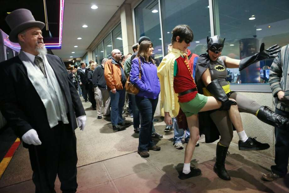 Spike O'Neill of KJR FM, left, watches as Chris Larson, dressed as Robin, and Kendra Frazer, dressed as Batman, get a bit rowdy while waiting to see Adam West, who played Batman, and Burt Ward, who played Robin during Emerald CIty Comicon's A Gotham Night in the Emerald City at Seattle's Cinerama. The actors attended a viewing of the 1966 theatrical Batman film on Friday, February 28, 2013 to help kickoff Comicon. (Joshua Trujillo, seattlepi.com)