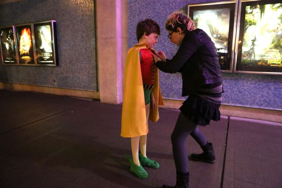 Aidan Vitti adjusts the Robin costume she made for Aidan Nelsen, 12, before they see Adam West, who played Batman, and Burt Ward, who played Robin during Emerald CIty Comicon's A Gotham Night in the Emerald City at Seattle's Cinerama. The actors attended a viewing of the 1966 theatrical Batman film on Friday, February 28, 2013 to help kickoff Comicon. (Joshua Trujillo, seattlepi.com)