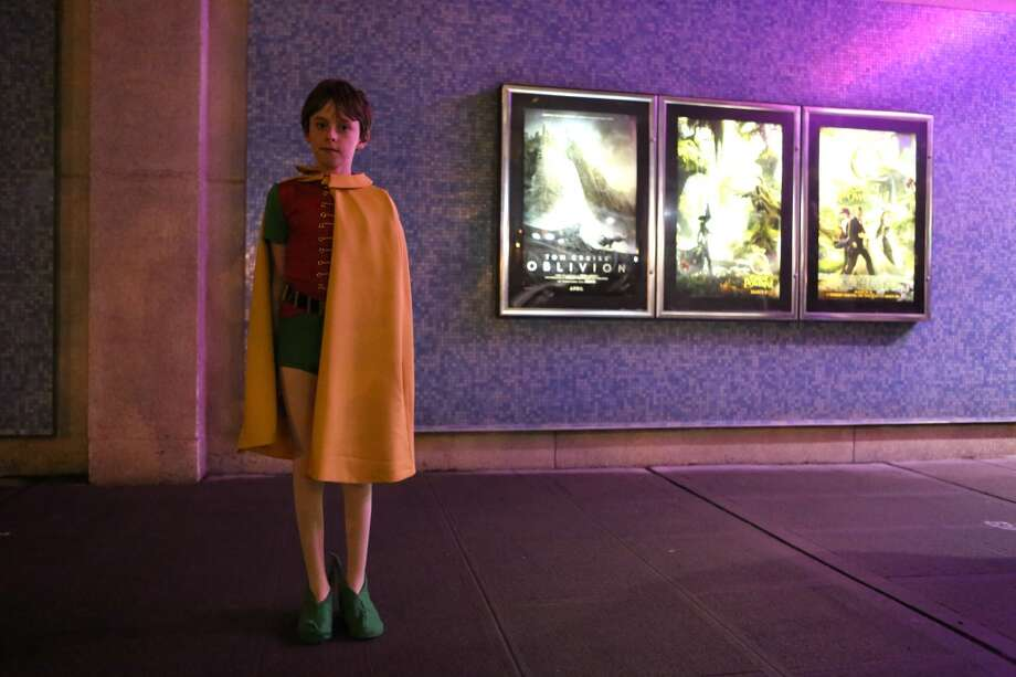 Aidan Nelsen, 12, wears a Robin costume before seeing Adam West, who played Batman, and Burt Ward, who played Robin during Emerald CIty Comicon's A Gotham Night in the Emerald City at Seattle's Cinerama. The actors attended a viewing of the 1966 theatrical Batman film on Friday, February 28, 2013 to help kickoff Comicon. (Joshua Trujillo, seattlepi.com)