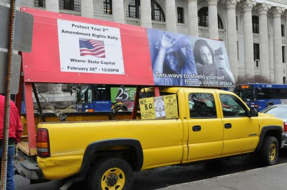 A truck with signs is parked on the street as the New York State Rifle & Pistol Association holds its 5th Annual Lobby Day and Rally at Capitol Park on Wednesday Feb. 27, 2013 in Albany, N.Y. (Lori Van Buren / Times Union)