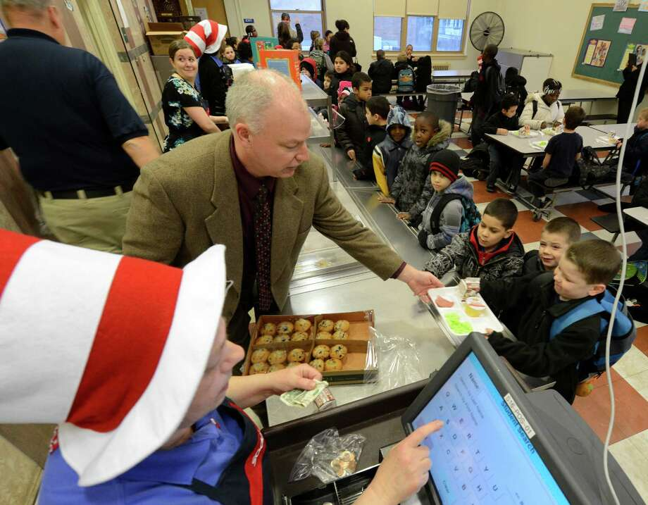 Bob Wood, director of food services for the Troy School District, hands out green eggs and ham on Friday, March 1, 2013 in the cafeteria at Troy, N.Y. P.S. 16 on the occasion of Dr. Seuss' 99th birthday.  (Skip Dickstein/Times Union) Photo: SKIP DICKSTEIN / 10021358A