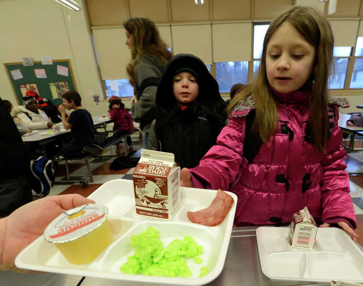 Makayla O'Brien-Cooper gets some green eggs and ham on Friday, March 1, 2013 in the cafeteria at Troy, N.Y. P.S. 16 on the occasion of Dr. Seuss' 99th birthday. (Skip Dickstein/Times Union)
