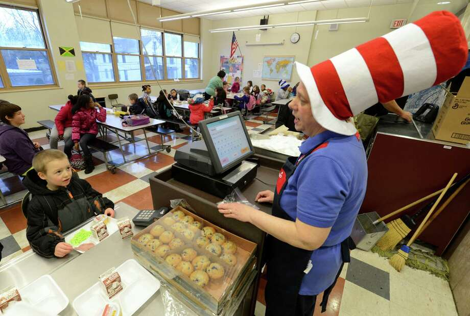 Jackie Hebert, right, cashes out a student who received some green eggs and ham on Friday, March 1, 2013 in the cafeteria at Troy, N.Y. P.S. 16 on the occasion of Dr. Seuss' 99th birthday.  (Skip Dickstein/Times Union) Photo: SKIP DICKSTEIN / 10021358A