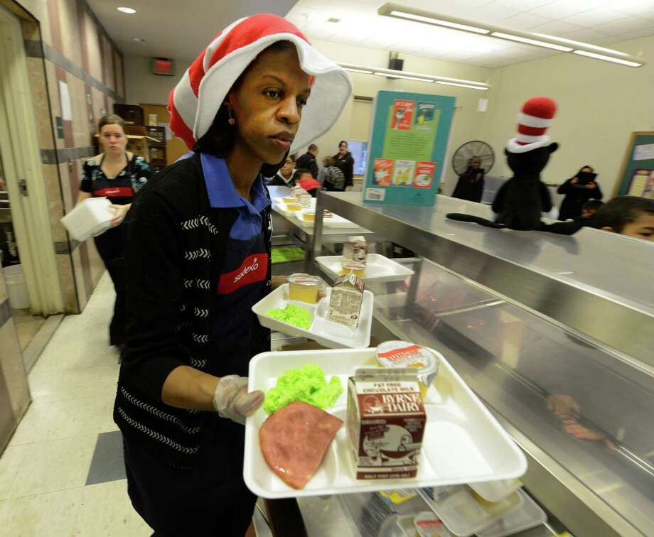 Food service worker Betty Bellamy rushes out some green eggs and ham on Friday, March 1, 2013 in the cafeteria at Troy, N.Y. P.S. 16 on the occasion of Dr. Seuss' 99th birthday.  (Skip Dickstein/Times Union) Photo: SKIP DICKSTEIN / 10021358A