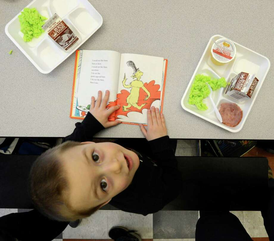 "James Sousie shows off his copy of ""Green Eggs and Ham"" as he eats some green eggs and ham on Friday, March 1, 2013 in the cafeteria at Troy, N.Y. P.S. 16 on the occasion of Dr. Seuss' 99th birthday.  (Skip Dickstein/Times Union) Photo: SKIP DICKSTEIN / 10021358A"