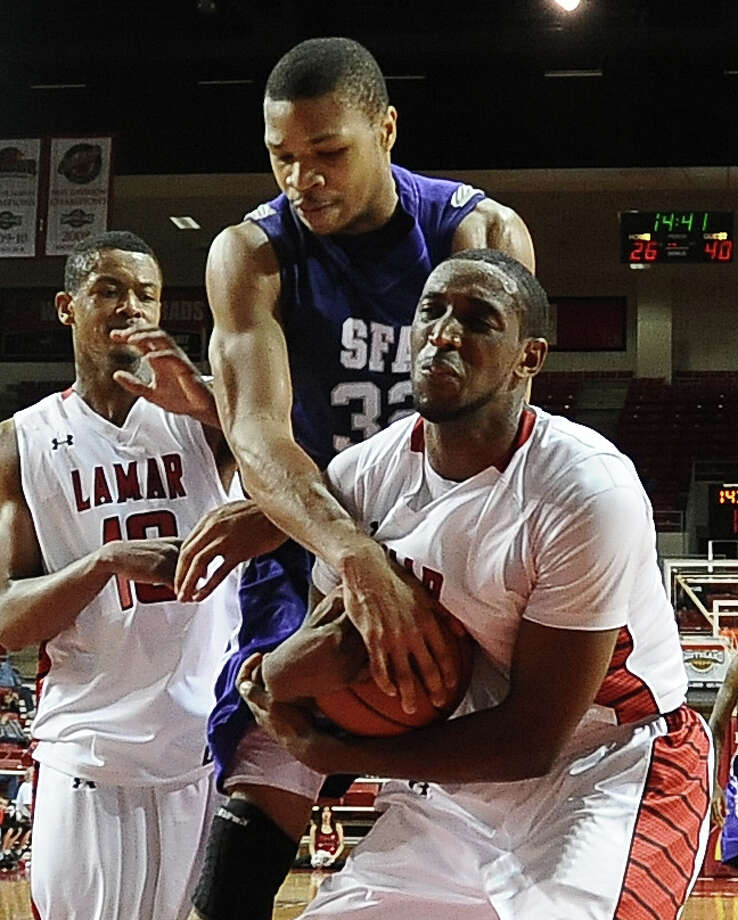 SFA player Taylor Smith, #32, tries to pry the ball away from Lamar player Stan Brown, #35, after a rebound during the Lamar University basketball game against Stephen F. Austin University on Saturday, Febuary 2, 2013, at the Montagne Center.  SFA won over Lamar 65 - 49. Photo taken: Randy Edwards/The Enterprise Photo: Randy Edwards