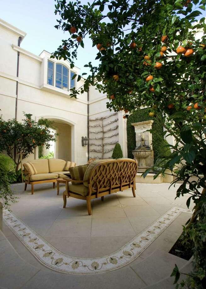 Espaliered Chinese fringe trees and mandarins accent a courtyard in this garden on the River Oaks Garden Club's Azalea Trail.  Photo: John Everett / John Everett