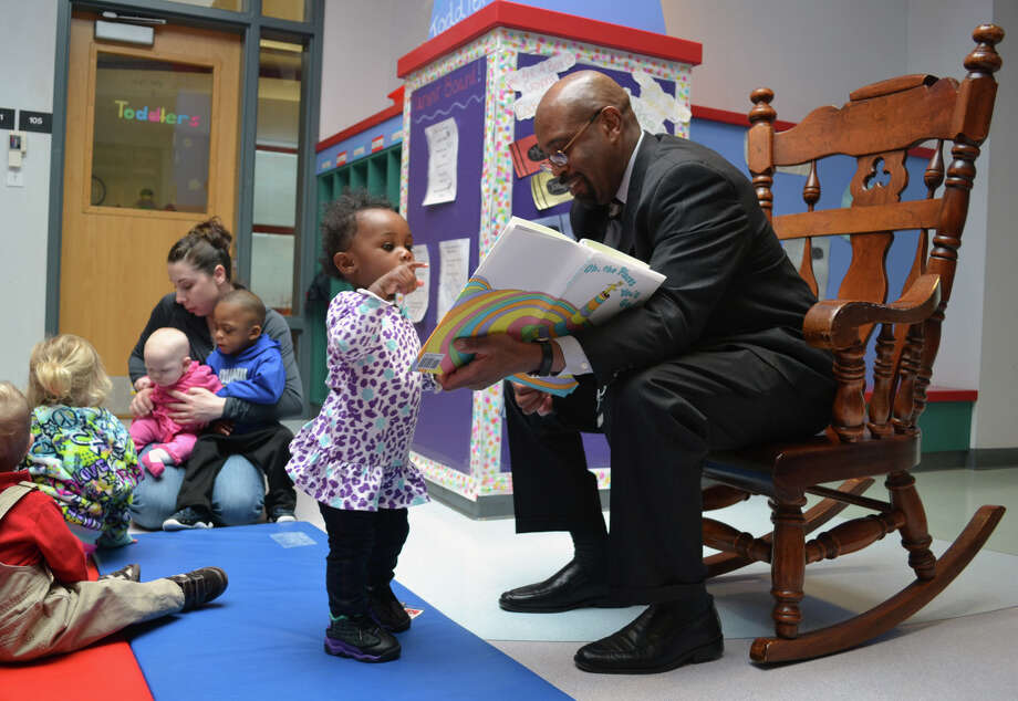 "Halo Johnson, age 18 months, listens as Dr. Quintin Bullock, president of Schenectady County Community College, reads ""Oh, the Places You'll Go"" by Dr. Seuss on Friday, March 1, 2013, at the YWCA Children's Center on the SCCC campus. (Schenectady County Community College photo)"