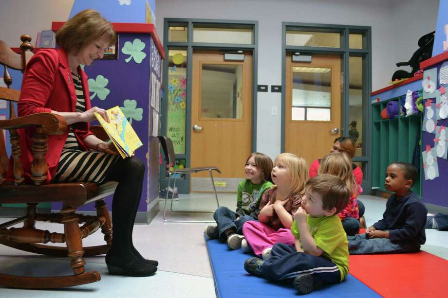 "Donna Tessitore, executive director of the Faculty Student Association of SCCC, reads ""I Can Read with My Eyes Shut"" by Dr. Seuss to children ages 3 to 4 years old on Friday, March 1, 2013, at the YWCA Children's Center on the SCCC campus. (Schenectady Community College photo)"