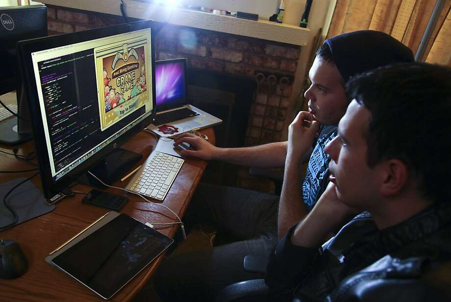 Cesar Miranda, left, and his brother Edgar, developers, work on their claw crane game at their home in San Jose, Calif., Feb. 6, 2013. With some states poised to clear the way for legal gambling on the Internet, Silicon Valley's traditional gaming companies are expanding to meet the expected deluge of players. (Jim Wilson/The New York Times) Photo: Jim Wilson, New York Times