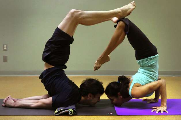 Alejandro Reyes, left, and Ana Hollis position in a Partner Chest Stand. Acrobatics coach Vladimir Vladev trains a small group of committed yoga enthusiasts in AcroYoga, at Yoga Shala Studio, which combines acrobatics and Yoga, on Tuesday, Feb. 26, 2013. Photo: Bob Owen, San Antonio Express-News / © 2012 San Antonio Express-News