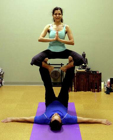 Acrobatics coach Vladimir Vladev trains a small group of committed yoga enthusiasts in AcroYoga, at Yoga Shala Studio, which combines acrobatics and Yoga, on Tuesday, Feb. 26, 2013. Ana Hollis , owner of Yoga Shala Studio, is supported by Vladev in a Seated Throne. Photo: Bob Owen, San Antonio Express-News / © 2012 San Antonio Express-News