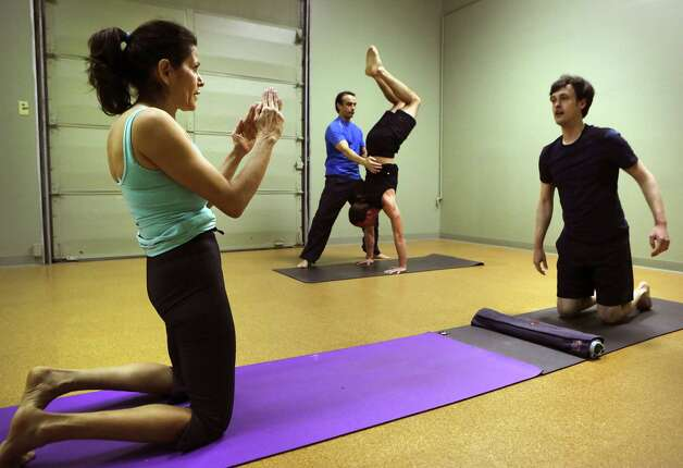 Acrobatics coach Vladimir Vladev trains a small group of committed yoga enthusiasts in AcroYoga, at Yoga Shala Studio, which combines acrobatics and Yoga, on Tuesday, Feb. 26, 2013. Ana Hollis, left, owner of the tudio, plans a position with Alejandro Reyes, right. Photo: Bob Owen, San Antonio Express-News / © 2012 San Antonio Express-News