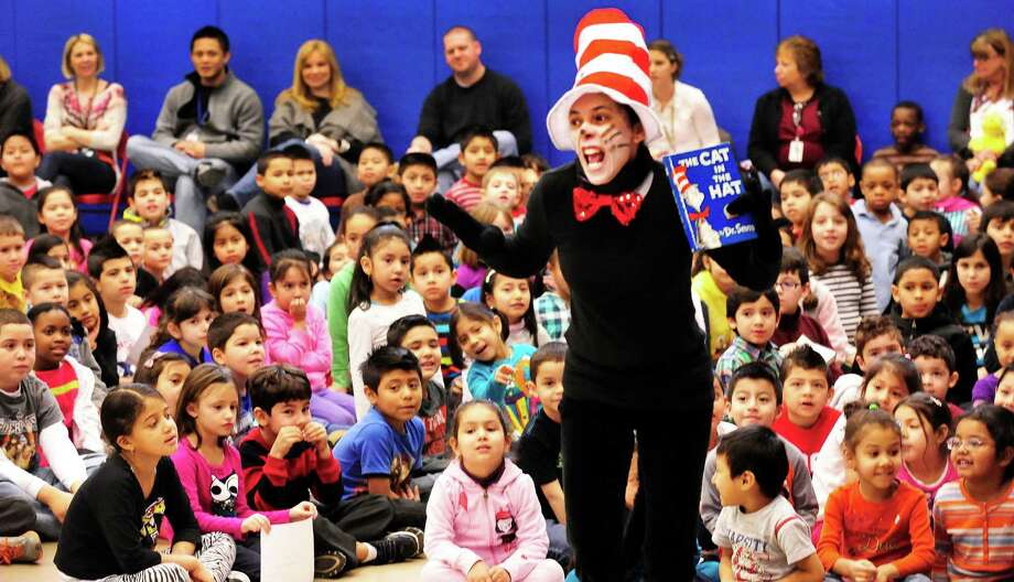 Teacher Rosiane Olivea portrays the Cat in the Hat during a celebration of Dr. Seuss' birthday, at Ellsworth Avenue School in Danbury, Conn.,. during a Read Across America event. A flash mob, led by pre-education students from Western Connecticut State University, surprised students at the end of an awards assembly Friday, March 1, 2013. Photo: Michael Duffy / The News-Times
