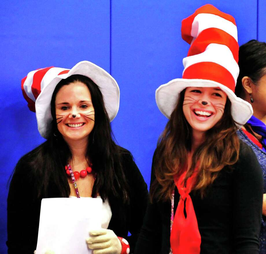 Teachers Lindsay Benicewicz, left, and Alexandra Kelleher, portray the Cat in the Hat during a celebration of Dr. Seuss' birthday, at Ellsworth Avenue School in Danbury, Conn.,. during a Read Across America event. A flash mob, led by pre-education students from Western Connecticut State University, surprised students at the end of an awards assembly Friday, March 1, 2013. Photo: Michael Duffy / The News-Times