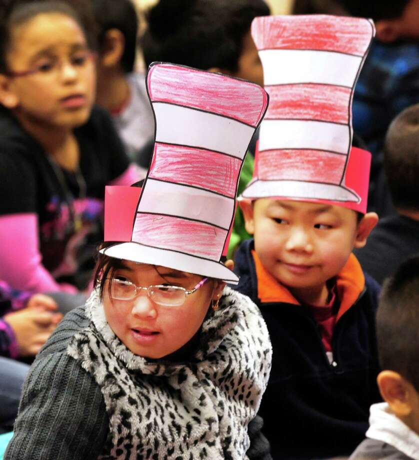 First grade students Madesha Rarn, left, and Vincent Ly, wear Seuss hats during a celebration of Dr. Seuss' birthday, at Ellsworth Avenue School in Danbury, Conn.,. during a Read Across America event. A flash mob, led by pre-education students from Western Connecticut State University, surprised students at the end of an awards assembly Friday, March 1, 2013. Photo: Michael Duffy / The News-Times