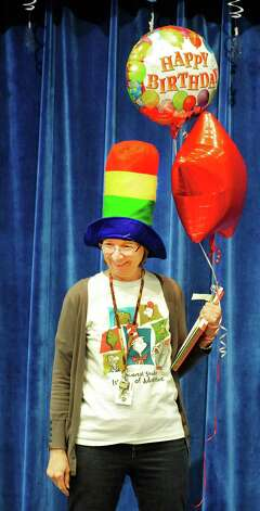 Reading Specialist Jan Edwards performs during a celebration of Dr. Seuss' birthday, at Ellsworth Avenue School in Danbury, Conn.,. during a Read Across America event. A flash mob, led by pre-education students from Western Connecticut State University, surprised students at the end of an awards assembly Friday, March 1, 2013. Photo: Michael Duffy / The News-Times