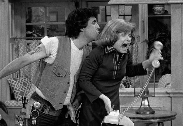 Schneider (Pat Harrington, Jr.) sneaks up behind Ann (Bonnie Franklin) as she attempts to make a phone call in a scene from the sitcom 'One Day at a Time,' 1975. Photo: CBS Photo Archive, Getty / 2005 CBS WORLDWIDE INC.
