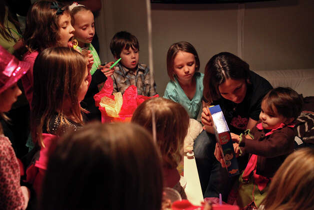 Marley Bedford, 3, far right, with her mother, Crystal Bedford, opens presents while friends and sister, Rory Bedford, 5, center, watch during her birthday party at Sweet Marley's in Fredericksburg on December 28, 2012. Photo: Lisa Krantz, San Antonio Express-News / © 2012 San Antonio Express-News